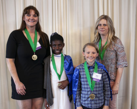 A group of 2 students and 2 teachers stands smiling at the camera with green medals around their necks.